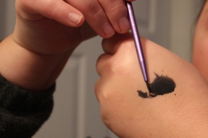 I then mixed the black shadow with water and used a thin liner brush to make the cat eyes.